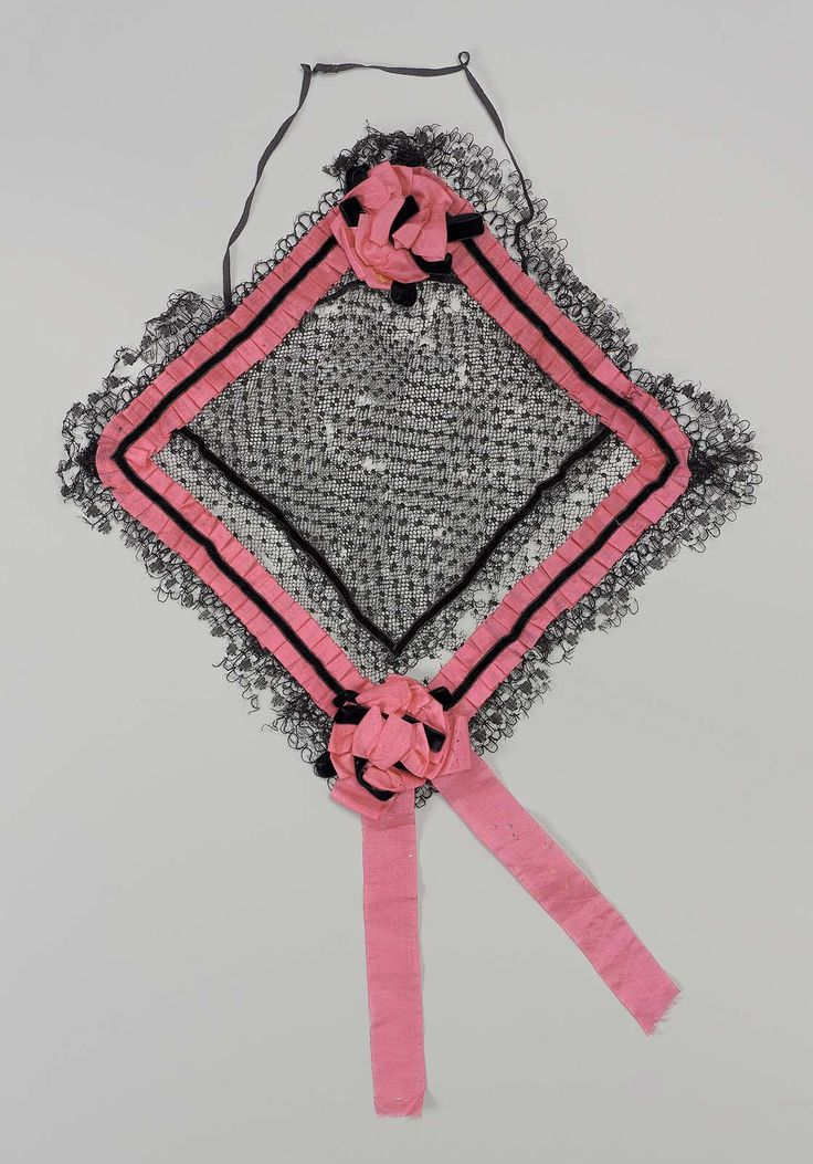 Cap; square, of black dotted net; trimmed on edges with pleated bright pink silk ribbon with narrow black velvet ribbon holding pleated ribbon in position; rosettes, of pink ribbon and black velvet ribbon, on two diagonally opposite corners; double flounce of narrow bobbin lace around outer edges; narrow black elastic attached to front point; designed to be worn around bun ofhair.