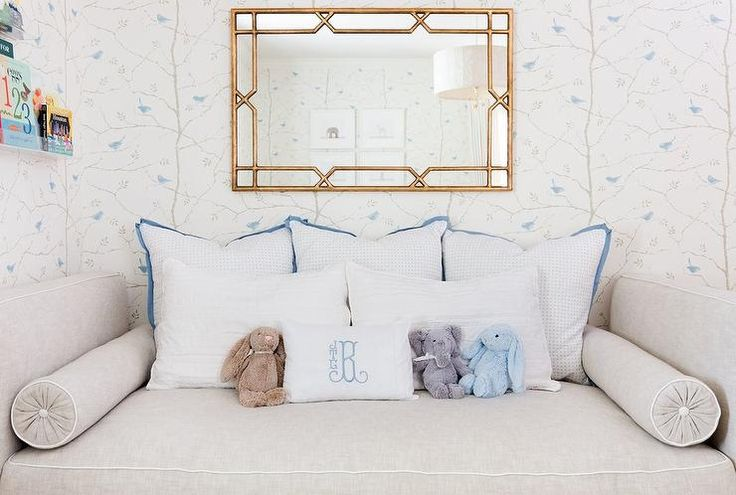 A gray daybed accented with white piping and matching bolster pillows is topped with blue and white pillows placed beneath a gold bamboo mirror mounted to a wall covered in Sanderson Dawn Chorus Mineral Blue Wallpaper in this gorgeous blue and white nursery.