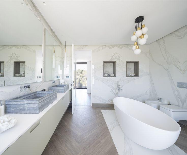 Baño de vivienda en Ibiza, diseñado por Natalia Zubizarreta Interiorismo. Mueble de baño en madera lacada con lavabos sobre encimera mármol gris. Grifería de pared. Espejos retroiluminados. Paredes en azulejo porcelánico gran formato imitación mármol. Baldosa porcelánica imitación madera en espiga. Bañera exenta resina de Kos. Focos integrados en techo. Foseado perimetral en techo retroiluminado. Luminarias suspendidas en dorado y blanco. Hornacinas decorativas en madera.