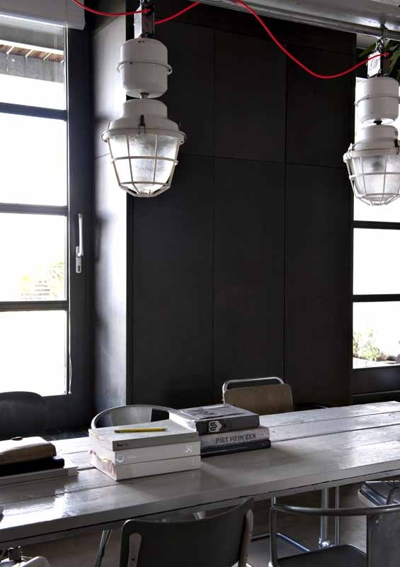 Industrial dining room - large hanging lights - metal chairs - white table - Black wall