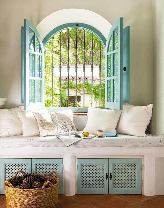 turquoise arched windows with shutters above built in seating area in natural cotten