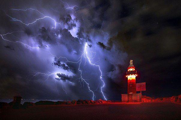 Фотограф заснял мощную вспышку молнии у маяка в гавани Фримантла (Западная Австралия).