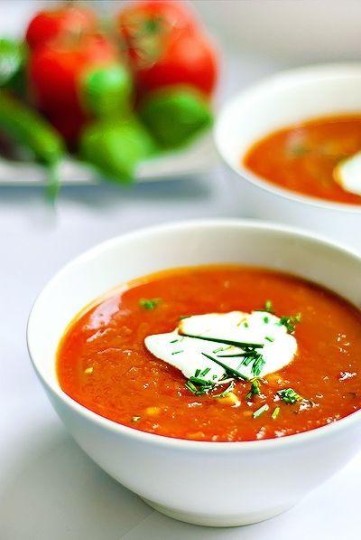 Bereiden:  Rooster de paprika's in de oven of boven het gasfornuis. Doe ze in een kom, dek af met plasticfolie en laat 5 minuten stomen. Verwijder de zwarte velletjes en snijd in stukjes.  Verhit de olie en bak hierin de ui met knoflook glazig. Voeg de tomatenstukjes en de paprika's toe en laat op een zacht vuurtje enkele minuten meebakken. Giet de bouillon erbij. Voeg de kruiden toe en breng op smaak met zout en peper. Laat de soep 20 minuten zachtjes pruttelen.  Pureer de soep m...