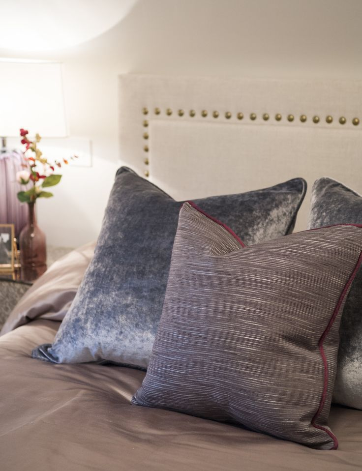 These opulent crushed velvet and robust, ottoman weave Zinc Textile #cushions add smokey accents to the neutral tones of this luxurious, bespoke #headboard with space-nailed detailing in sandstone. #interiordesign #luxurylife #luxury #london #luxuryproperty #luxuryhomes #londonproperty #luxuryinteriors