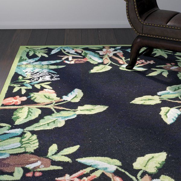 This Black/Green Novelty Area Rug looks timeless when placed in your living space. This rug features a colorful floral print, which perfectly contrasts with the black background. This combination of colors blends well with contemporary as well as traditional interiors. Made from 100% wool, this rug sturdy and durable. This hand-hooked rug has a cotton backing that adds to its durability. It needs a rug pad under it to ensure that it does not slip. This Black/Green Novelty Area Rug i...