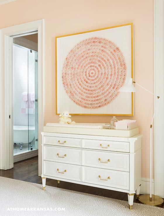 Melissa Haynes - White and pink girl's nursery features a wall painted pinkish orange, Benjamin Moore Queen Anne Pink, lined with a white french dresser as changing table placed under a pink art piece in a gold leaf frame illuminated by a white and gold swing arm floor lamp.