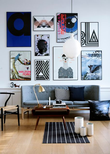 Gallery wall of medium-sized art, all in thin black frames, and all with a black, white or blue base