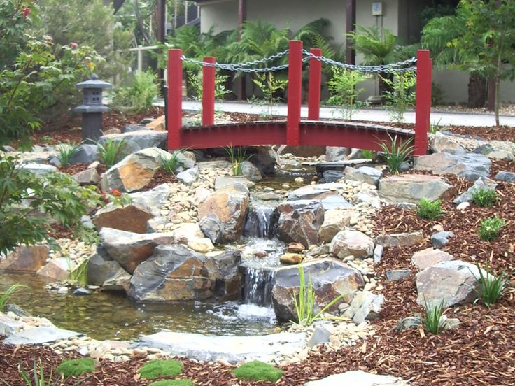 Cascading waterfalls running under a red, arched, timber bridge in a Japanese style garden.