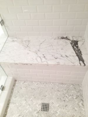 Use of cheaper subway tile on wall with a touch of marble. Bang for buck!