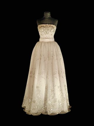 1984 - WORN BY QUEEN SILVIA OF SWEDEN TO NOBEL BANQUET. WHITE TULLE EMBROIDERED WITH SILVER DETAILS ON THE BODICE, WHICH ARE REPEATED ON THE OVERSKIRT MADE OF MOIRE SILK. DESIGNED BY JORGEN BENDER.