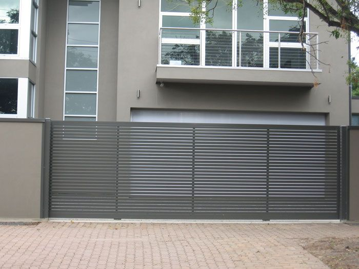 This gate and fence have a modern look that goes well with the design of the house. I like how the gate is kind of see through and how to tubs make it look modern. But it is nice that the fence is solid and strong. It seems like a great combination of home protection and curb appeal.