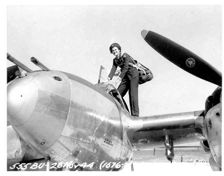 WASP pilot Ruth Dailey climbing into a P-38 Lightning aircraft, 28 Nov 1944.