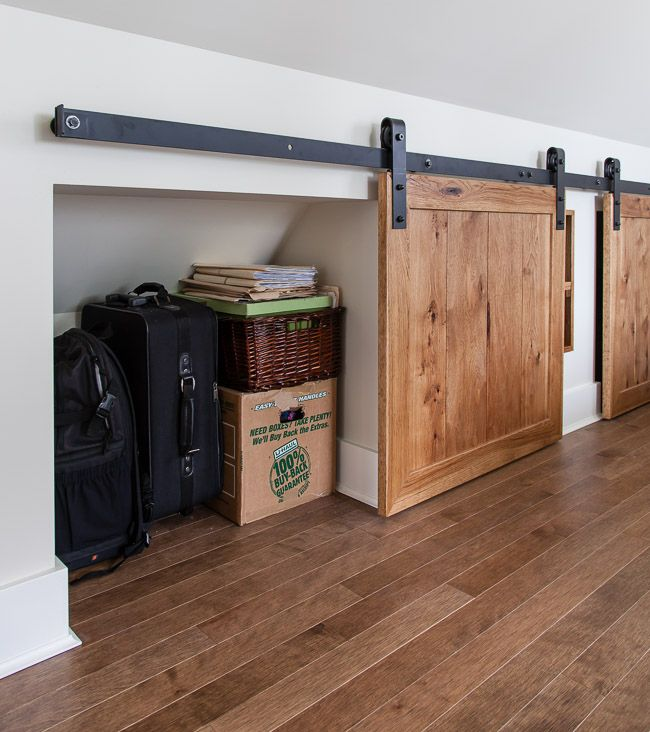Dead space under the eaves becomes a focal point and smart storage area with the addition of custom mini barn doors. See more of this fabulous redo at http://thehousediaries.com/blog/2015/1/7/jan-7-big-bedroom
