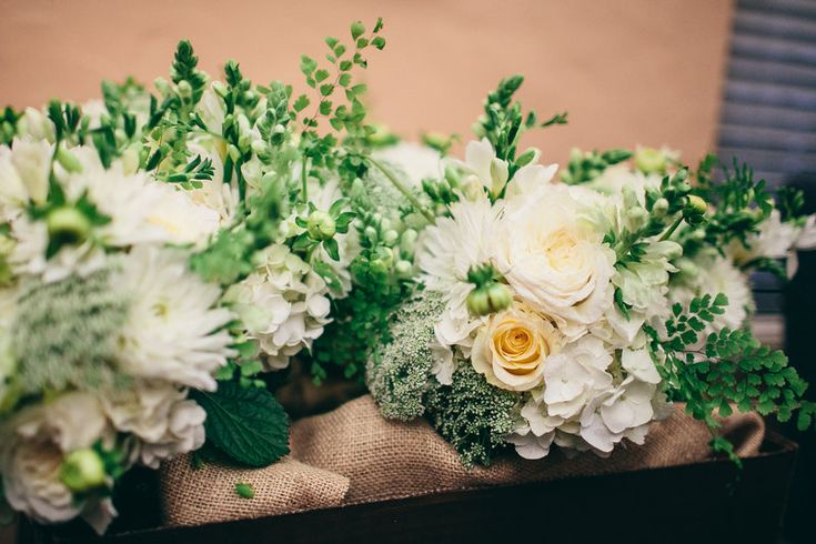 Detail of bridesmaids bouquets composed of white dahlia, white ranunculus, white rose, white hydrangea, white snapdragon , maidenhair fern, bupleurum and Queen Anne's lace.