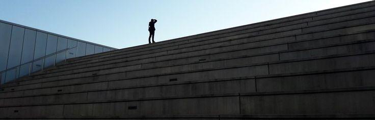 Ramon sobre las escaleras frente a la Torre Agbar fotografiando el atardecer tras el mercat dels Encants de Barcelona.