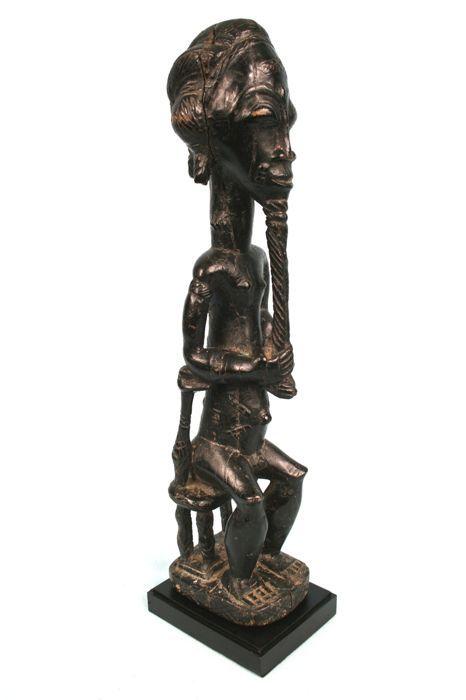 Prachtige Asie Usu Fetish - BAULE - Ivoorkust  Asie Usu fetish van de stam Baule.Amazing vertegenwoordiging zeer fijn gesneden.Het standbeeld is seatted op een Akan stoel. Het heeft een extreem lange Beer. Fijne tribal littekens zijn bijna overal in het lichaam aanwezig.Een klein deel van de basis ontbreekt en er is een scheur aan de rechterkant met blijkbaar lichte inheemse reparaties.Het standbeeld is gemonteerd op de stand van een professionele kwaliteit.Rond de jaren 60.Total met houten…