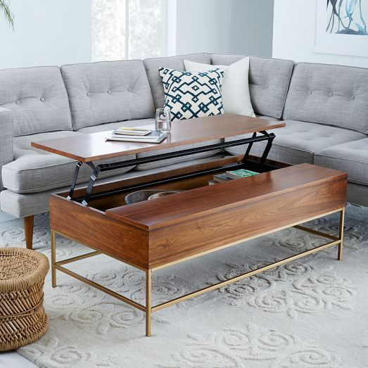 Secret stasher. One side of the Storage Coffee Table's top pops up to reveal a boatload of hidden storage. Lofted on airy steel legs, the walnut stained body has enough room to stow anything from toys and remotes to pillows and throws.