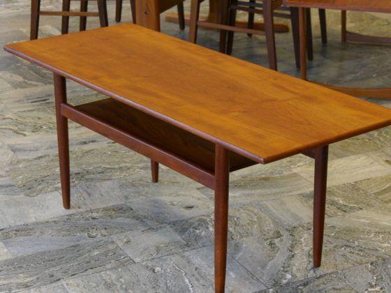 Danskt soffbord i teak med runda ben samt tidningshylla.  Etikettmärkt.  125x49x51 cm