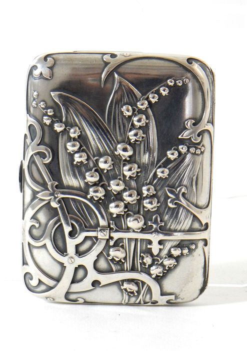 Beautiful cigarette case made of silver. Designed and made by the French silversmith Charles Murat who worked in Paris around 1897. Beautifully decorated with Lily of the valley flowers. Inside with vermeil. Various silver marks, i.a. the crab, and CM for Charles Murat. In addition, the reference déposé.  Condition: - fine, beautiful original condition.  Dimensions: - 8 x 6 x 1 cm.  Shipment: - registered, insured, and properly packaged.