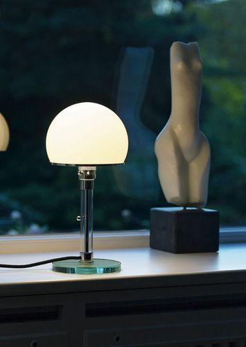 Bauhaus Lampe med glas fod og glasrør Bauhauslampen af Wilhelm Wagenfeld, 1923 Den lille bordlampe er blevet berømt som stilikon for Bauhaus-stilen. Foden og røret er fremstillet i glas. Lampeskærmen er lavet af opalglas.