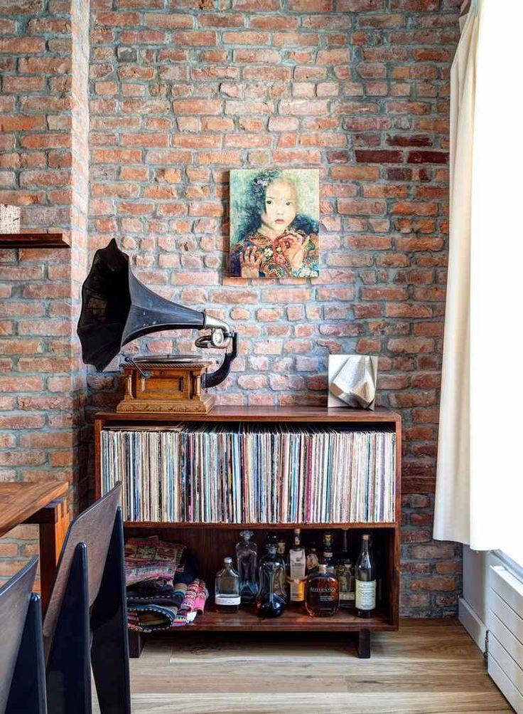 rangement vinyle : meuble en bois massif, tourne-disque ancien, brique de parement rouge et tableau décoratif