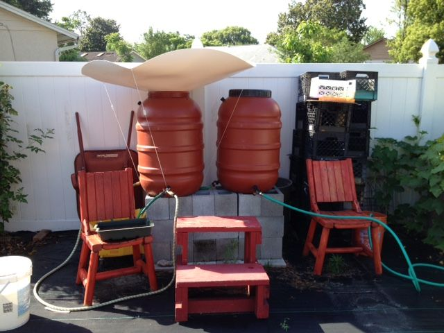 """Customer in Orlando, FL writes """"I have installed my rainsaucer and like it very much... I have 2 rain barrels side-by-side near my garden planter which is quite a ways from the house, so it wasn't possible to have the rain barrels filled from a gutter down spout. The barrels are linked together at the bottom so that as one fills the other fills also, and likewise, as one drains down, the other does, too."""""""