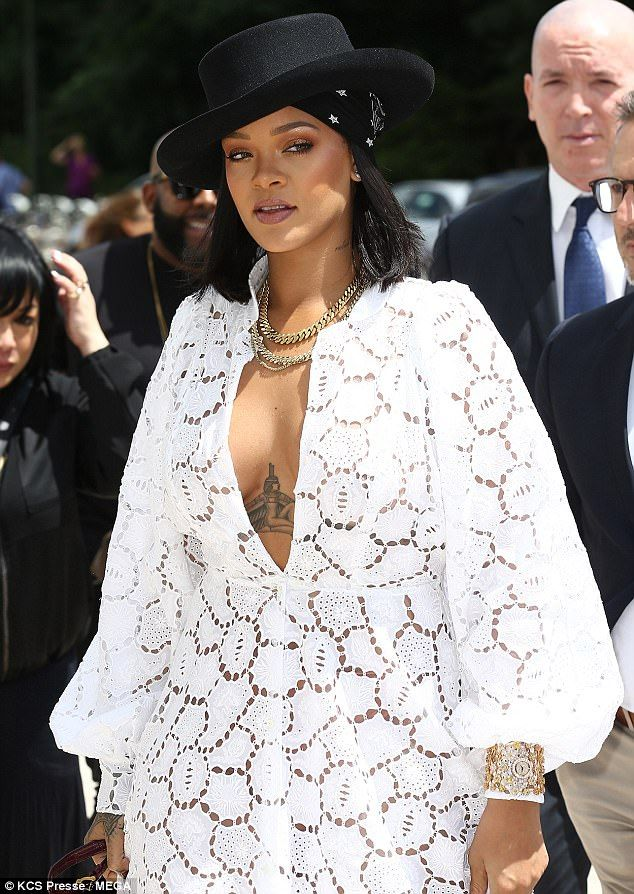Stunning: The Work hitmaker, looked stunning as she flashed her ample cleavage and intricate chest tattoo in the flowing ivory lace number, which plunged to her midsection