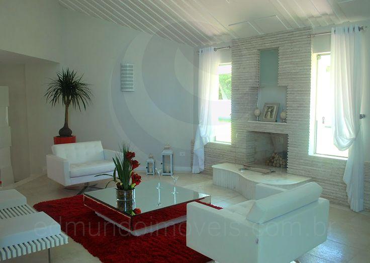 A decoração combina duas cores extremamente elegantes – branco e vermelho, com peças de design moderno como as poltronas e o pufe em frente à lareira.