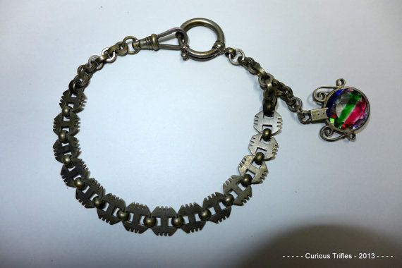 """Unusual Victorian Watch Chain with Colorful Fob sold on Etsy by curioustrifles.  This is an Unusual Victorian Watch Chain with Colorful Fob. The chain has an intriguing paneled chain, with a highly unusual glass gem stone that has 3 streaks of colors. Marked """"Gesetz geschützt"""" which is German, and means """"Protected by law"""""""