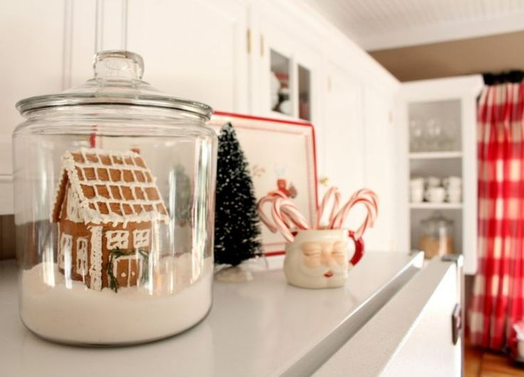 gingerbread house in large glass jar with fake snow -- so cute for a kitchen decoration at Christmas