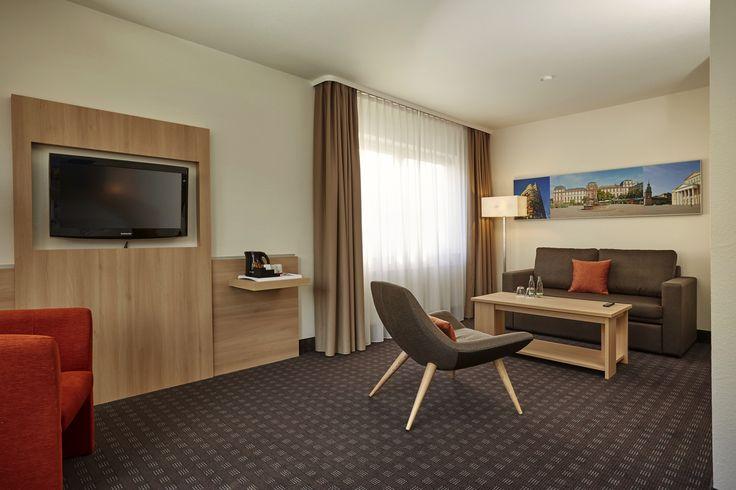 Die Suiten haben eine gemütliche Sitzecke mit Sofa, stylischem Sessel und Couchtisch - H+ Hotel Darmstadt