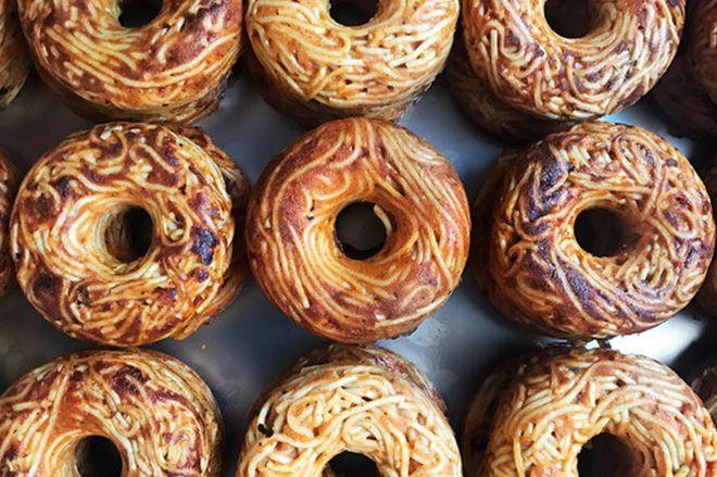 """ニューヨークの有名なフードマーケット「Smorgasburg」で販売されるという『Pop Pasta』によるユニークなハイブリッドフードをご紹介。タイトルにもある通り、そのユニークなハイブリッドフードとはパスタとドーナツをかけ合わせた""""スパゲッティドーナツ""""。元来のドーナツとは異なり、揚げるのではなく焼かれて調理されるそのドーナツは、パルメジャーノチーズ、卵、オリーブオイル、ガーリック、スパイスで味付けされた""""Aglio e Olio Pop""""やトマトピューレが加えられた""""Red Sauce Pop""""、ズッキーニが加えられた""""Zucchini Pop""""、ベーコンが加えられた""""Carbonara Pop""""、そして""""Red Sauce Pop""""にひき肉が加えられた""""Bolognese Pop""""などといった多くの種類がラインアップ"""