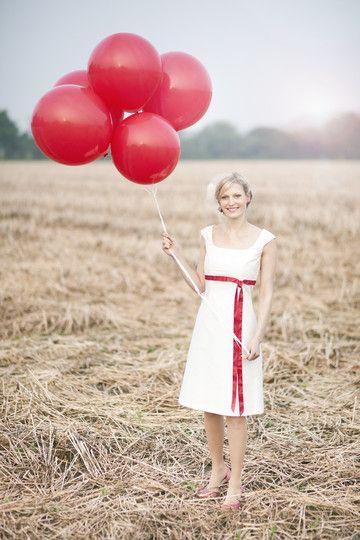 knielanges brautkleid mit pink- rotem bindeband, besticktes oberteil mit carrée ausschnitt mit trägern, leicht ausgestellter a- rock, rote luftballons passend zum band