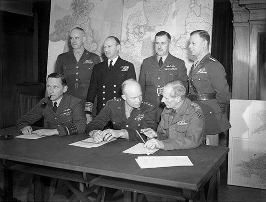 Allied leaders, clockwise from top left are: Lieutenant-General Omar Bradley, Commander, 1st US Army; Admiral Sir Bertram Ramsay, Naval Commander-in-Chief; Air Chief Marshal Sir Trafford Leigh-Mallory, Air Commander-in-Chief; Lieutenant-General Walter Bedell Smith, Chief of Staff; General Sir Bernard Montgomery, Commander, 21st Army Group (all Allied land forces); General Dwight D. Eisenhower, Supreme Commander; Air Chief Marshal Sir Arthur Tedder, Deputy Supreme Commander.