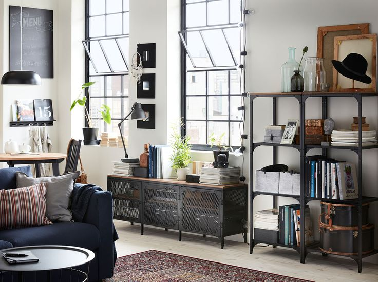 A living room with shelving units and a TV bench in black metal and wood in a converted warehouse-style building.