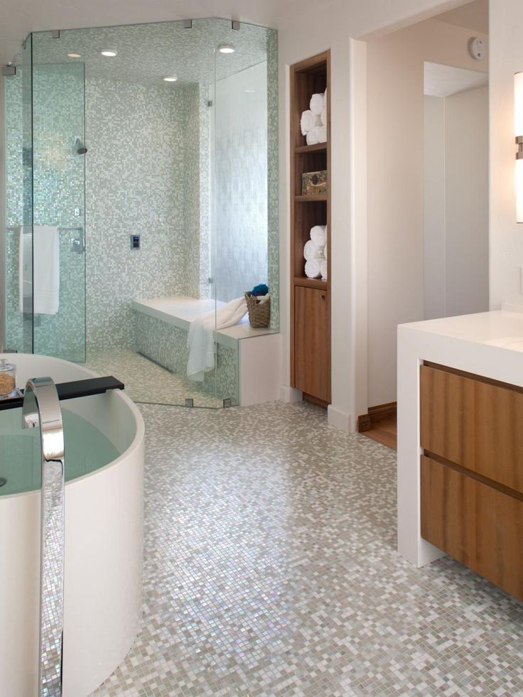 gray and white mosaic tile seamlessly climbs up the shower wall from the floor creating a