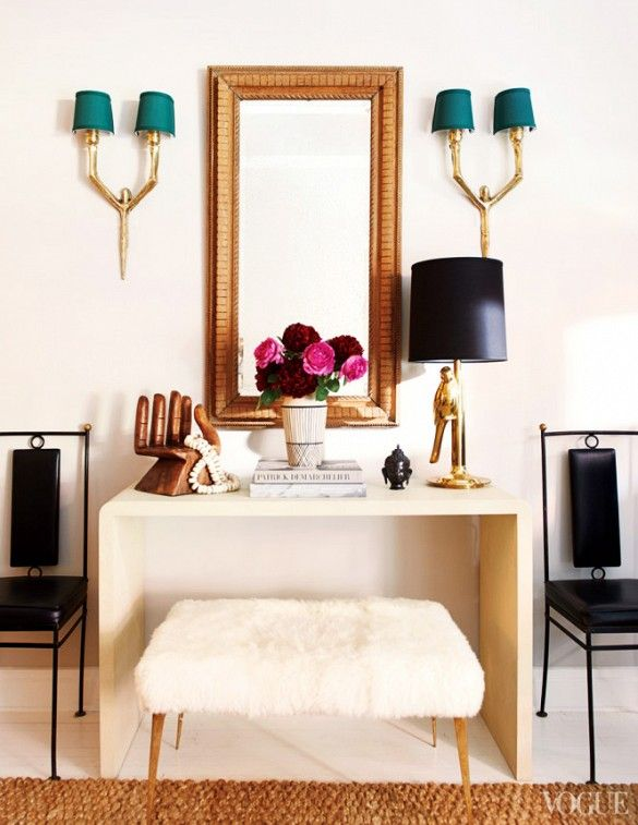 A vignette in Karlie Kloss' New York home with wooden hand sculpture, black and brass table lamp, and wall sconces.