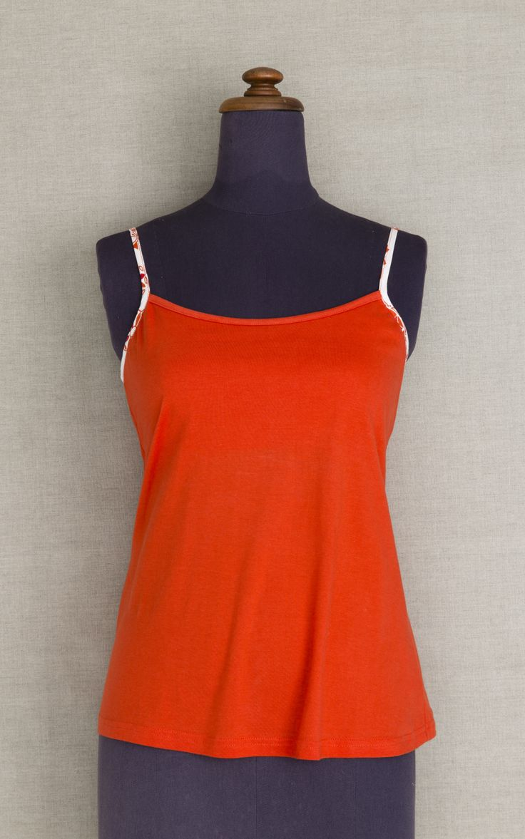 Moonbird Red cotton pyjama top. Strappy vest top with binding on straps and back is made from soft 100% GOTS certified organic cotton jersey, with hidden support layer made from cotton lycra. Binding is made from woven organic cotton in Desert Sun print. Moonbird garments are dyed and assembled in a Fair trade facility in jaipur, India. $49 AUD