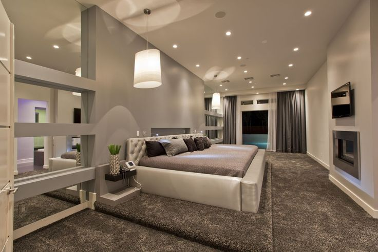 contemporary bedroom with carpeting and wall fireplace
