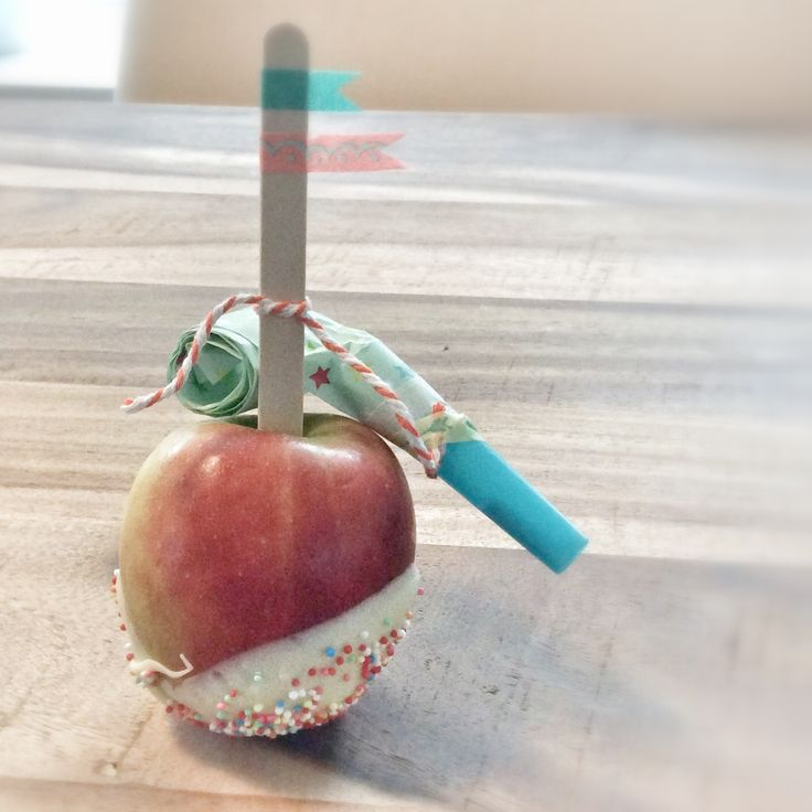 Apple on a stick, dipped in white chocolate and some sprinkles added