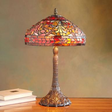 """Warm hues of rose, gold and blue in hand-soldered stained glass upon a graceful vintage-style base revive the Tiffany tradition. Perfect as accent lamp or on the bedside table. Imported. 12""""W x 12""""D x 18""""H."""