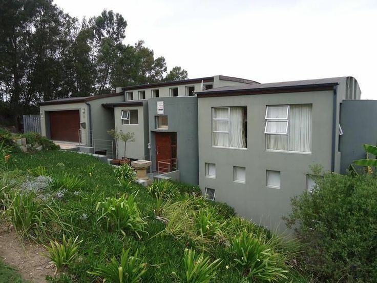 The unique shaped roof structure adds a unique feature to this property for sale in Knysna. It consists of three bedrooms, three modern tiled bathrooms plus study downstairs and the upper level houses the hub of the home – Open plan oak veneer kitchen with separate scullery which open-plans to spacious lounge/dining room and leads onto veranda with built in braai. High ceilings and lots of windows afford a spacious light atmosphere. Gorgeous lagoon views out towards the famous Knysna Heads…