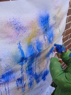 Peindre avec des vaporisateurs d'eau coloré est autrement plus amusant! À faire l'été avant la baignade...