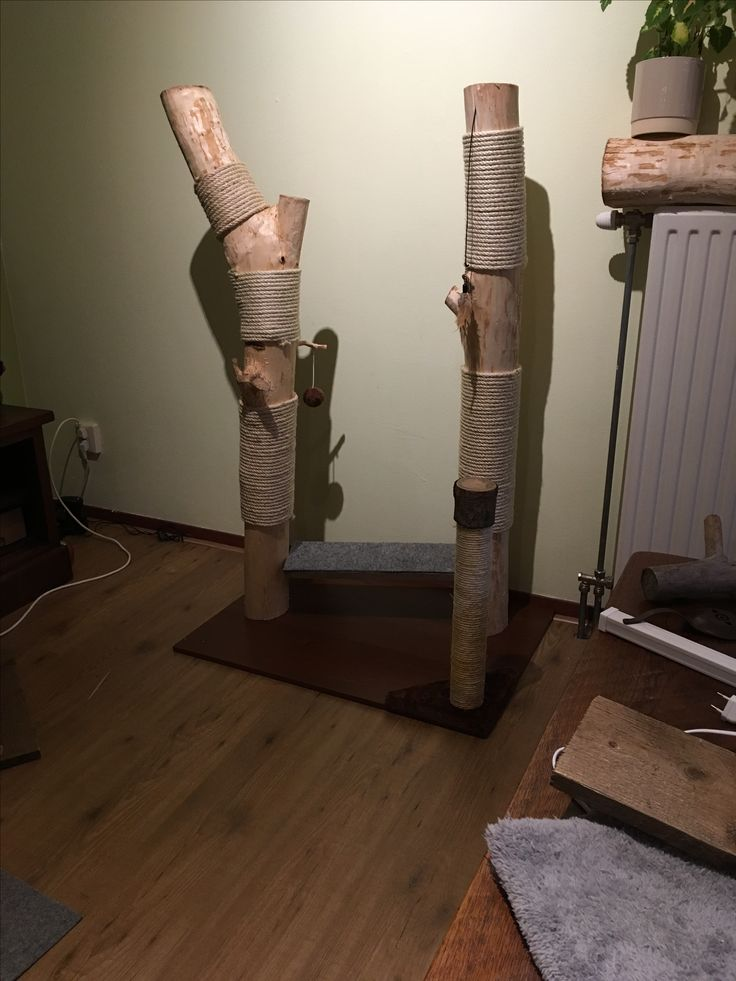 Scratching post made of wood and rope, standing on part of a used ikea closet door cut in half.