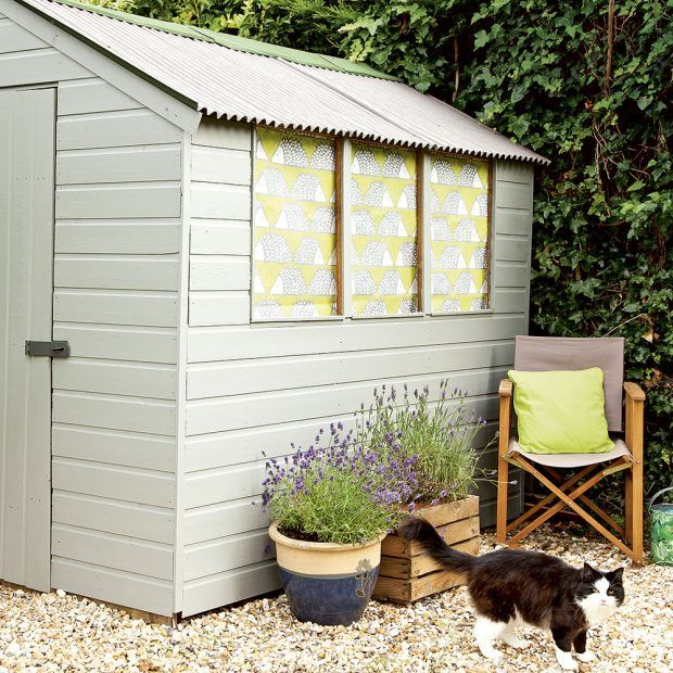 Transform a shed with a fresh coat of paint. This small garden features a gravel seating area with potted lavender and a shed fitted with patterned fabric at the windows for a homely touch. Add a bright cushion for a splash of colour.