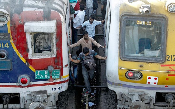 Definitely don't try this at home. Commuters try to cross railway tracks as trains wait in a suburban station in Mumbai