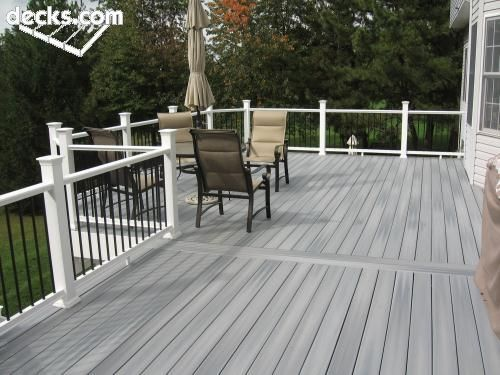 gray deck with white posts and black spindles by eddie