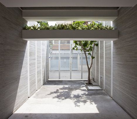 Concrete planters span between the side walls to cover the front and back facades of this Vietnamese house.