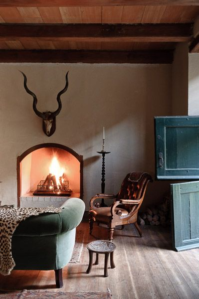 Masculine Simplicity; Fireplace, Animal Head & Horns, & Antique furnishings. By designer Adriaan Louw.
