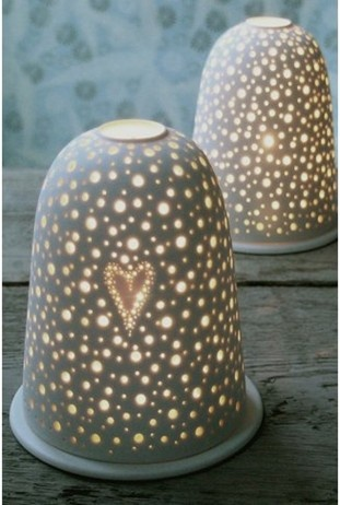 white semi porcelain tea light holder with tiny holes pierced all over letting the candle light flicker through and dance on the surrounding walls.